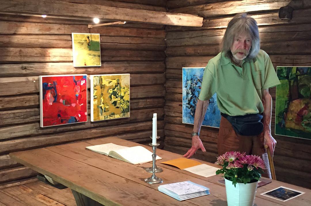 Kunstner med malerier i bakgrunnen. Foto.